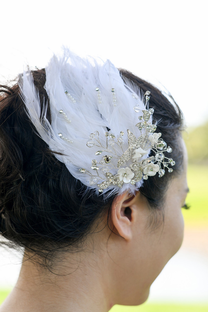 Detail of the hair piece of the bride made of white feathers and pearls