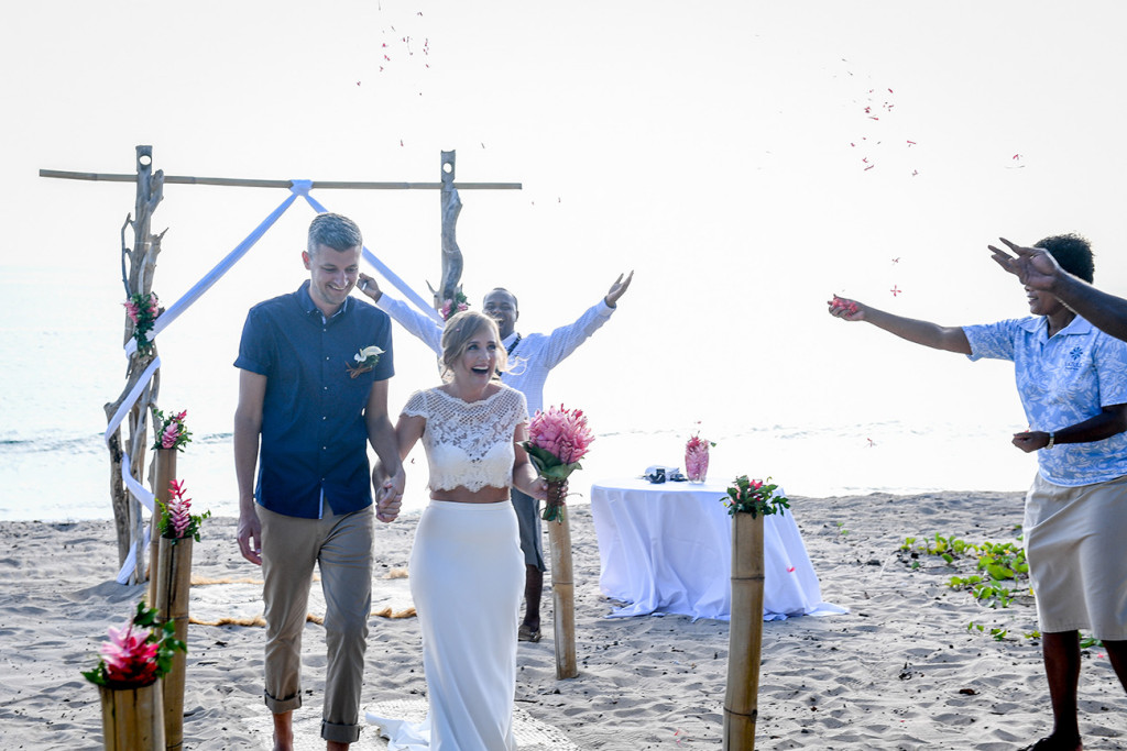 Bride and groom walk down aisle in Yatule Fiji Beach elopement