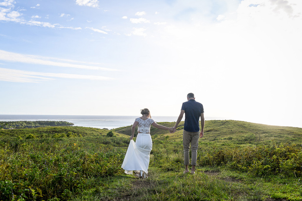 Bride and groom elope in green Fiji landscape walking into the Sunset