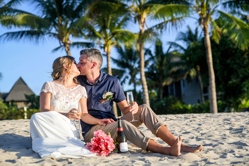 Eloped couple kiss on the beach with champagne on Coral Coast Fiji