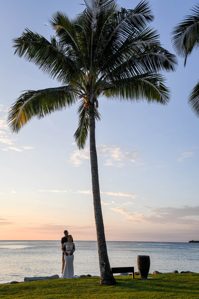 Eloped couple against palm trees in Yatule Fiji Resort