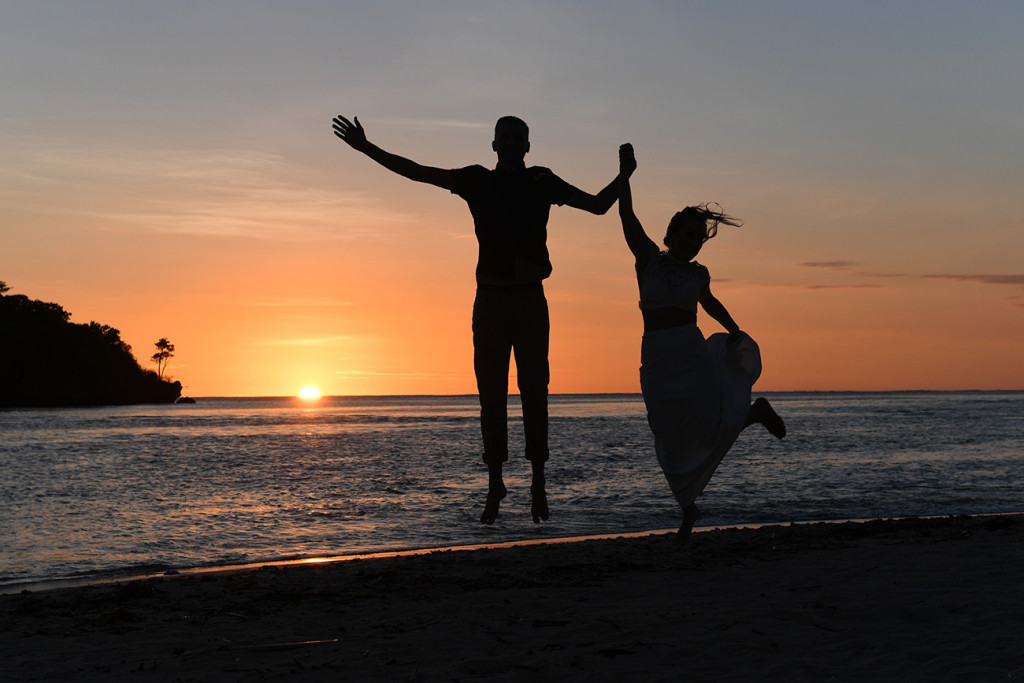 Silhouette of eloped couple jumping in sunset in Fiji Yatule Resort Beach