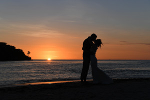 Silhouette kiss of eloped couple against Golden sunset on Coral Coast Fiji