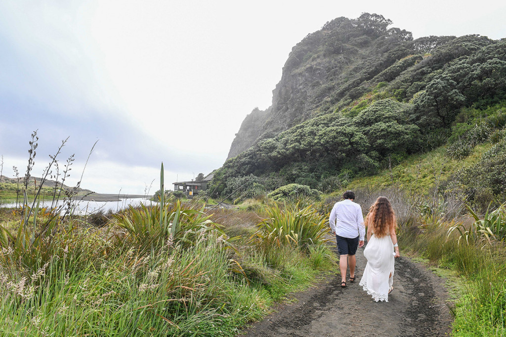 Eloping couple walk down the beach of Karekare NZ