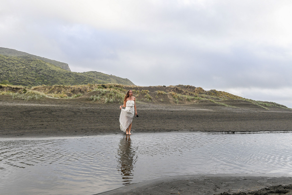 The beautiful bride dances on the black sand beach of Karekare New Zealand