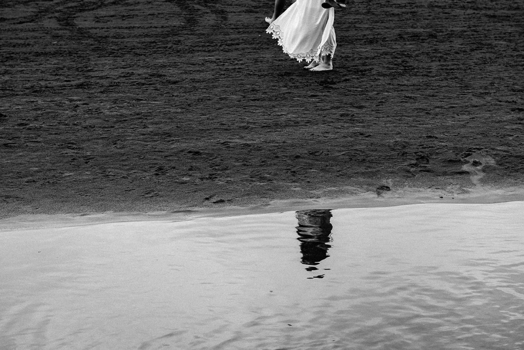 A reflection of the eloped couple on the black sand beaches of Karekare New Zealand