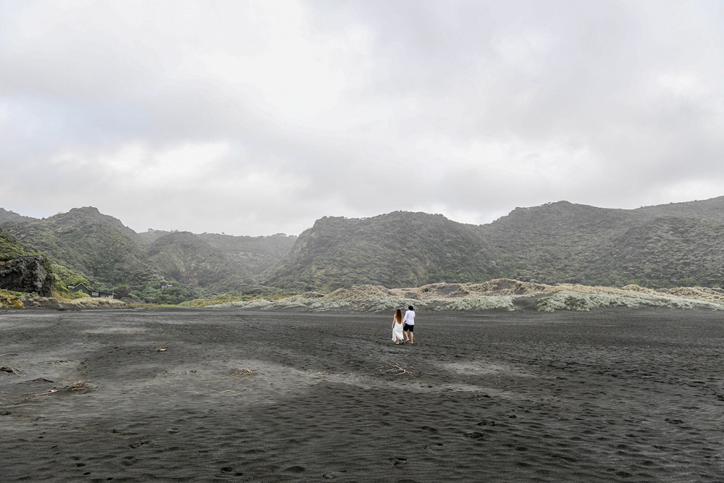 Wide Landscape shot of eloped couple on Black sand beaches of Karekare