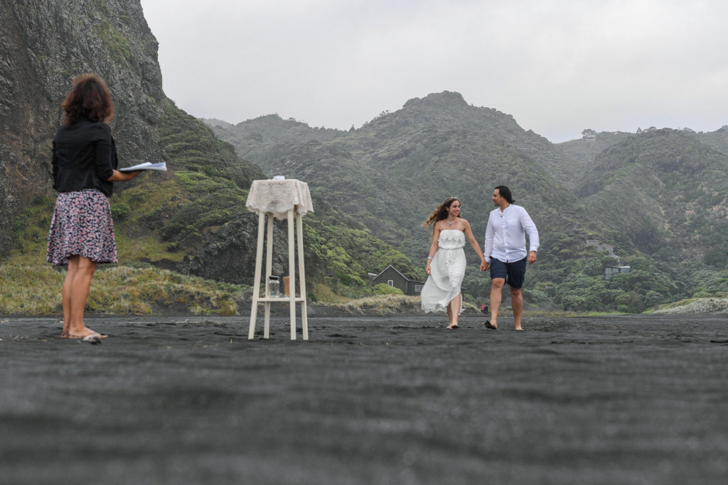 Eloped couple walking towards the ceremony ground on Karekare black sand beach New Zealand