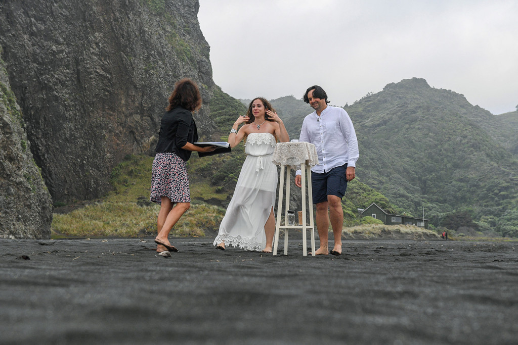 Celebrant and couple in elopement wedding ceremony on the Black sand beach of Karekare NZ
