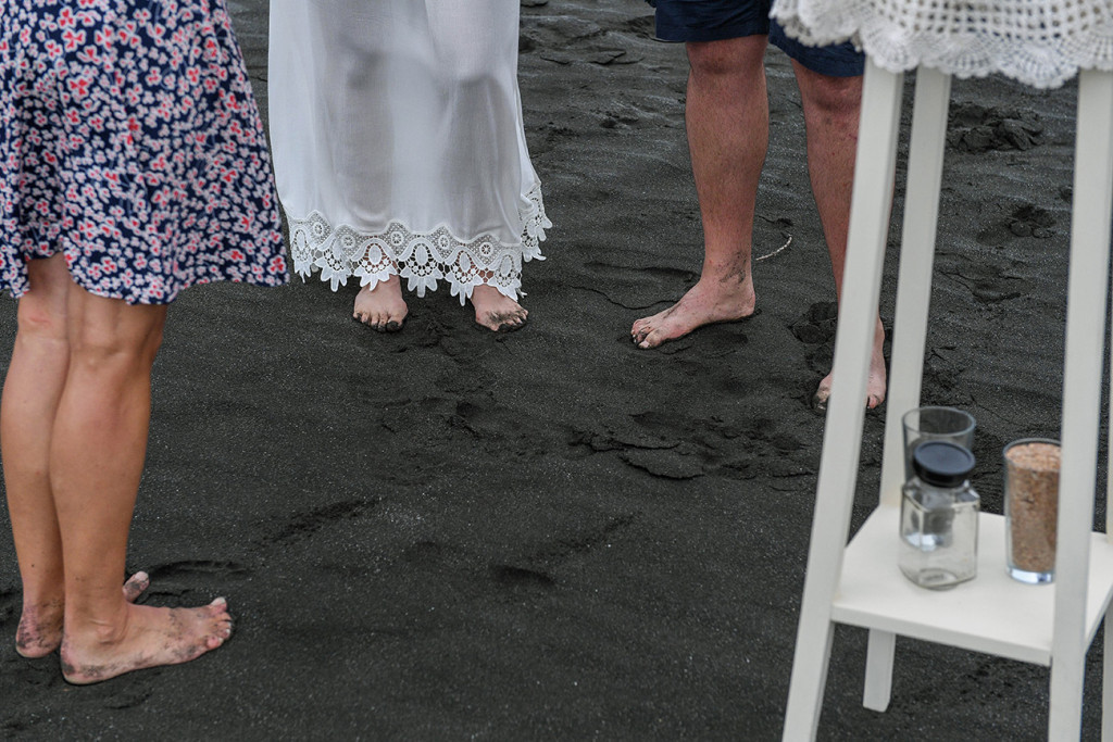 Eloped couple feet in black sand beach of Karekare Auckland New Zealand