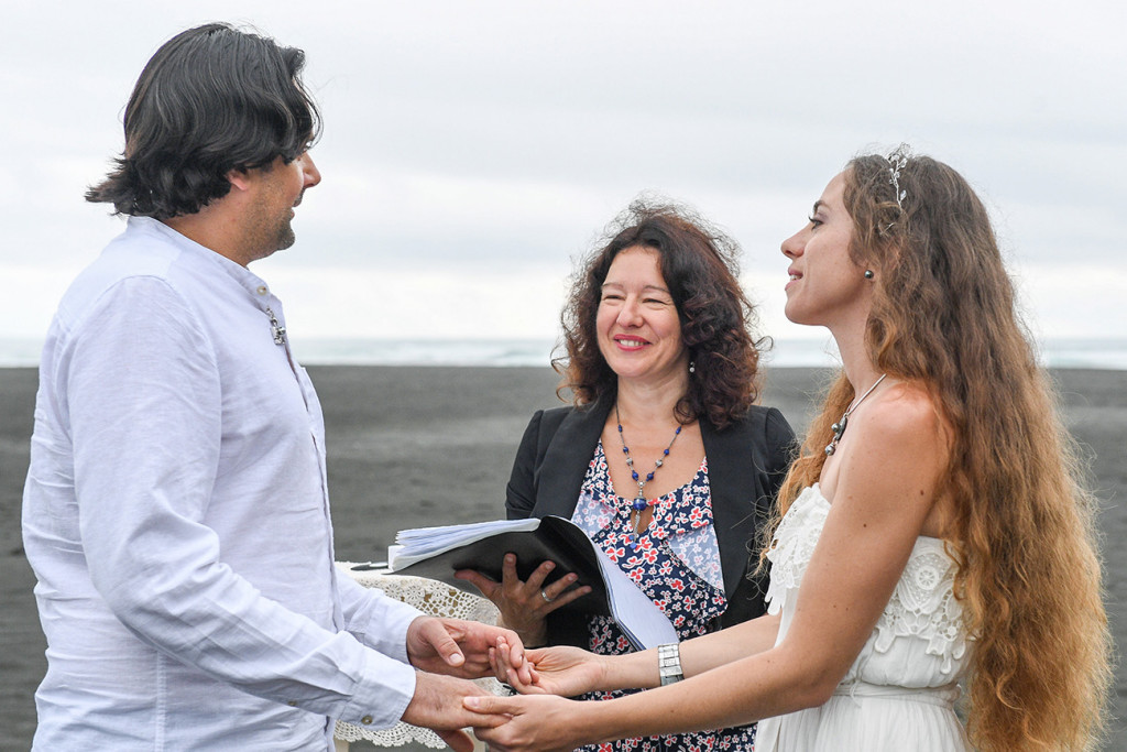 Eloped couple at altar of their black sand beach at Karekare Auckland New Zealand