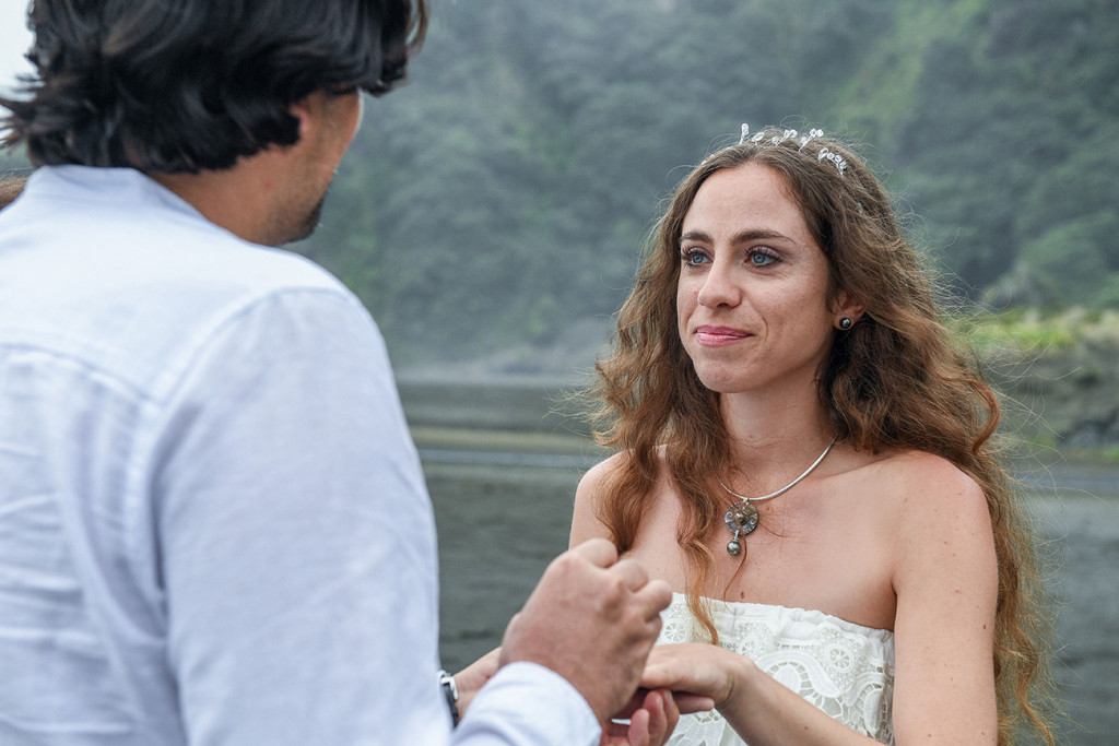 Bride wears ring on elopement wedding ceremony at Karekare Beach Auckland New Zealand