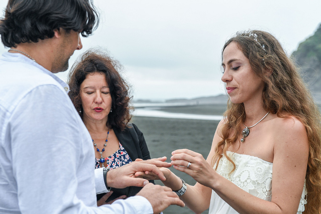 Groom wears ring at Karekare Beach Auckland New Zealand