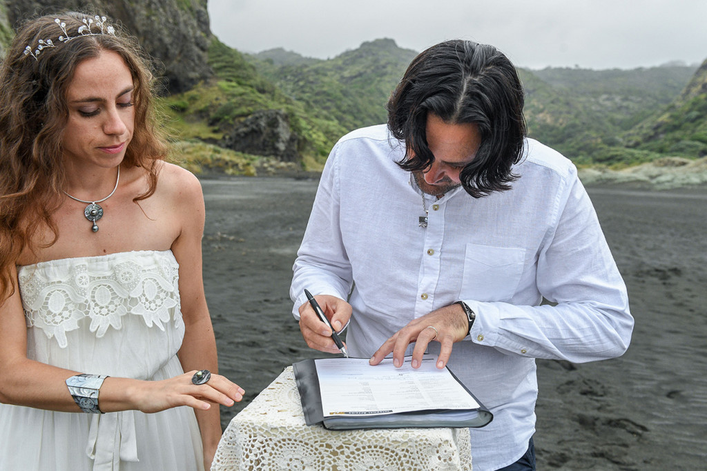 Groom signs marriage certificate in Karekare Beach Auckland NZ