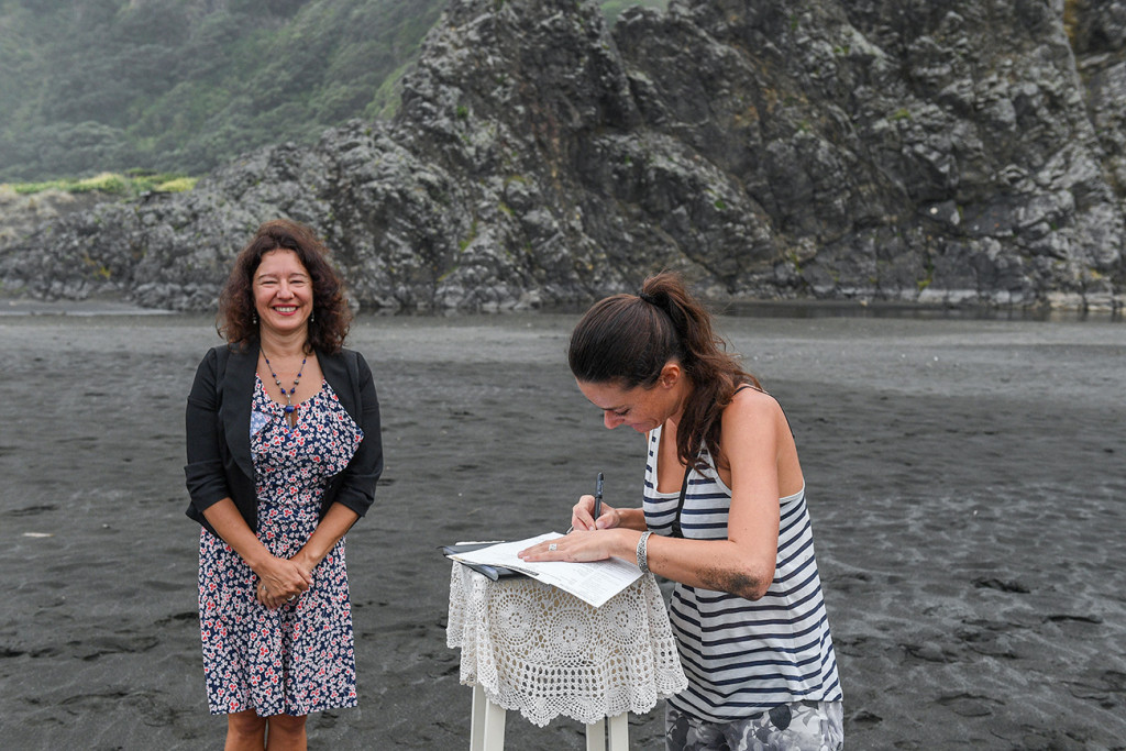 Photographer Anais Chaine signs marriage certificate as witness in elopement wedding at Karekare Beach Auckland NZ