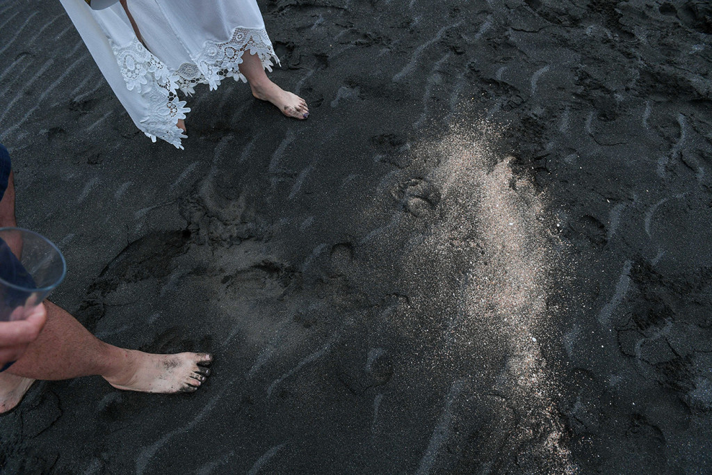 Newly eloped couple walk on Black sand beaches of Karekare Auckland NZ