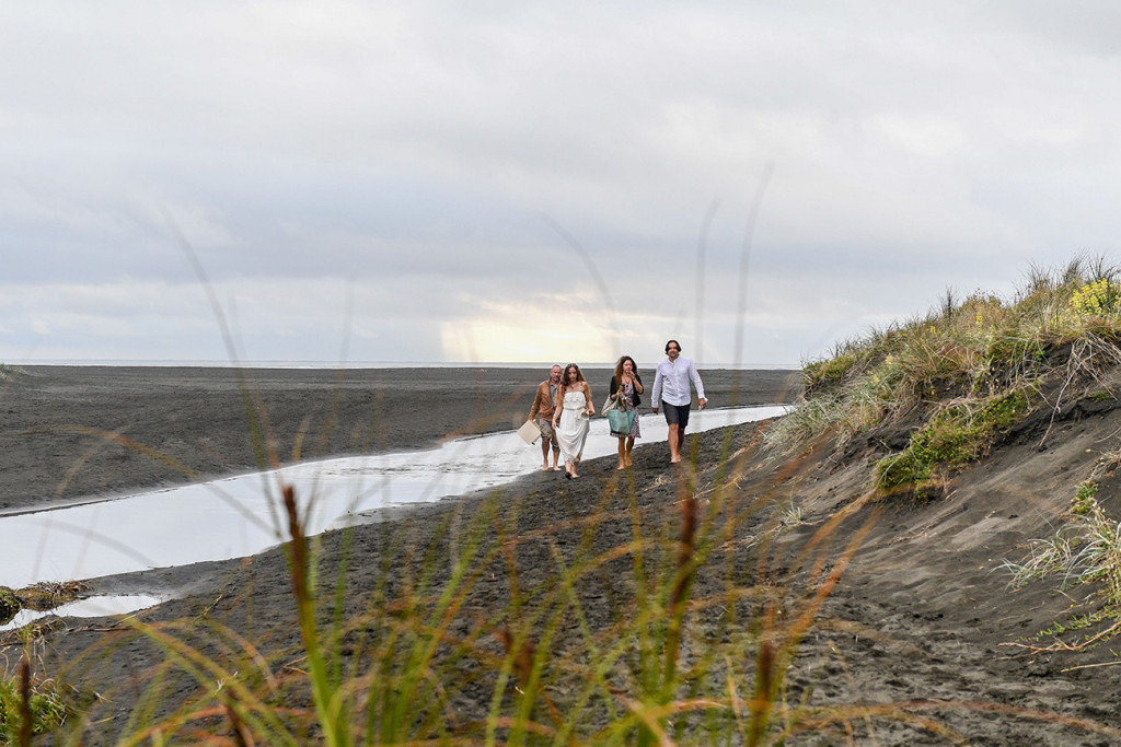 Newly married couple, celebrant and witness walk on Black sand beaches of Karekare Auckland NZ