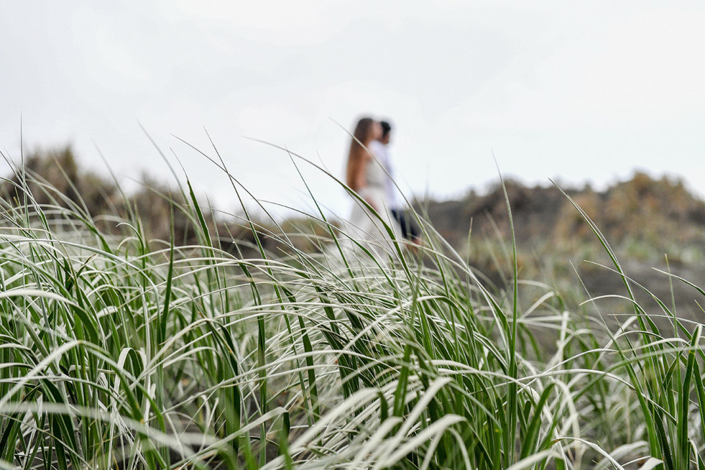 Bride and groom stroll in grass at Karekare Beach Auckland NZ