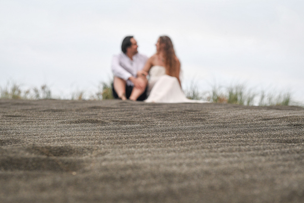 Bride and groom sit on the black sand beaches of Karekare NZ Auckland