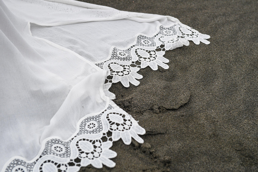 Lace detail on the bride's gown on the shores of Karekare Beach, Auckland NZ