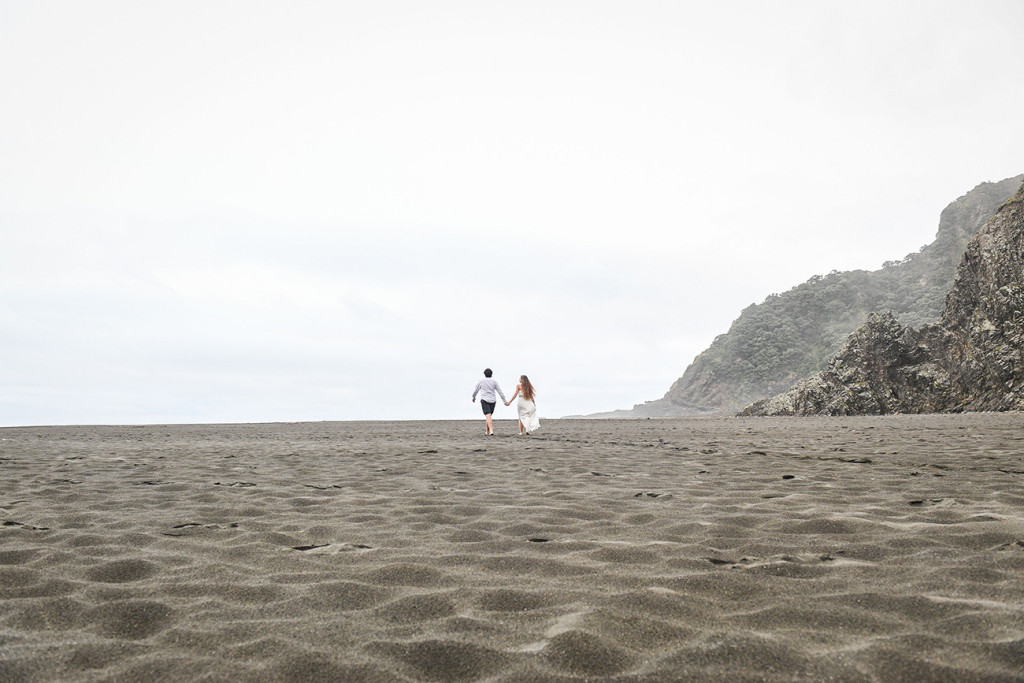 The eloped couple walk off into the horizon at Karekare Beach Auckland NZ