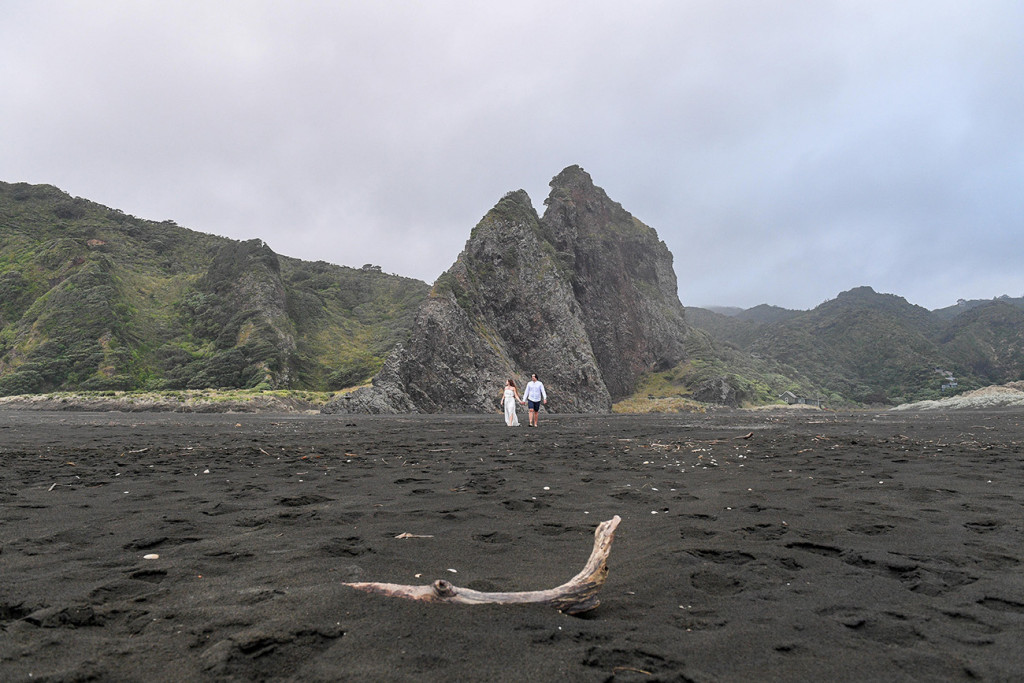 Landscape shot of Newly eloped couple on black sand beaches of Karekare NZ