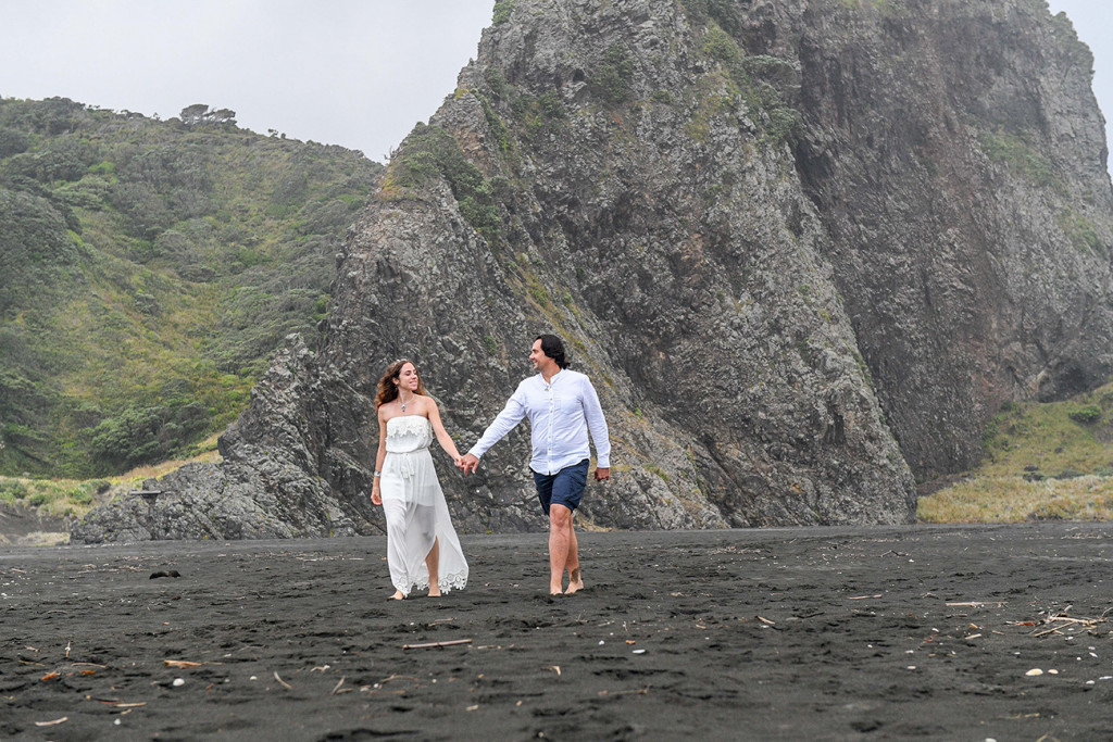 The newly married couple stroll together on the beach of Karekare NZ Auckland
