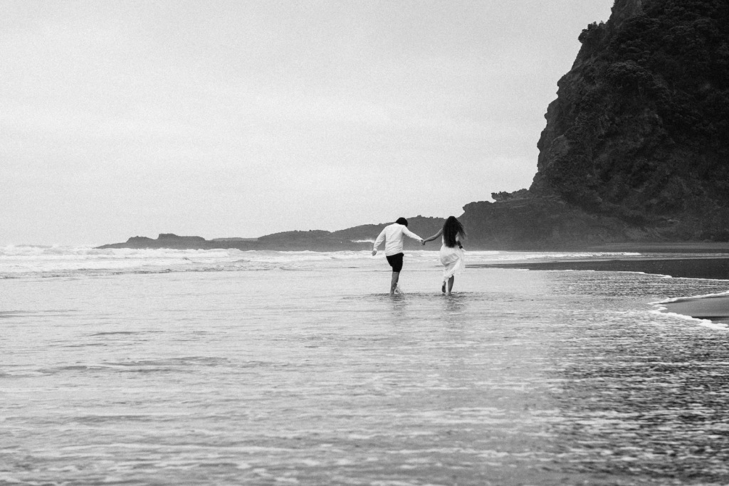 Black and white photo of newly eloped couple walking into the sea Karekare Beach Auckland NZ