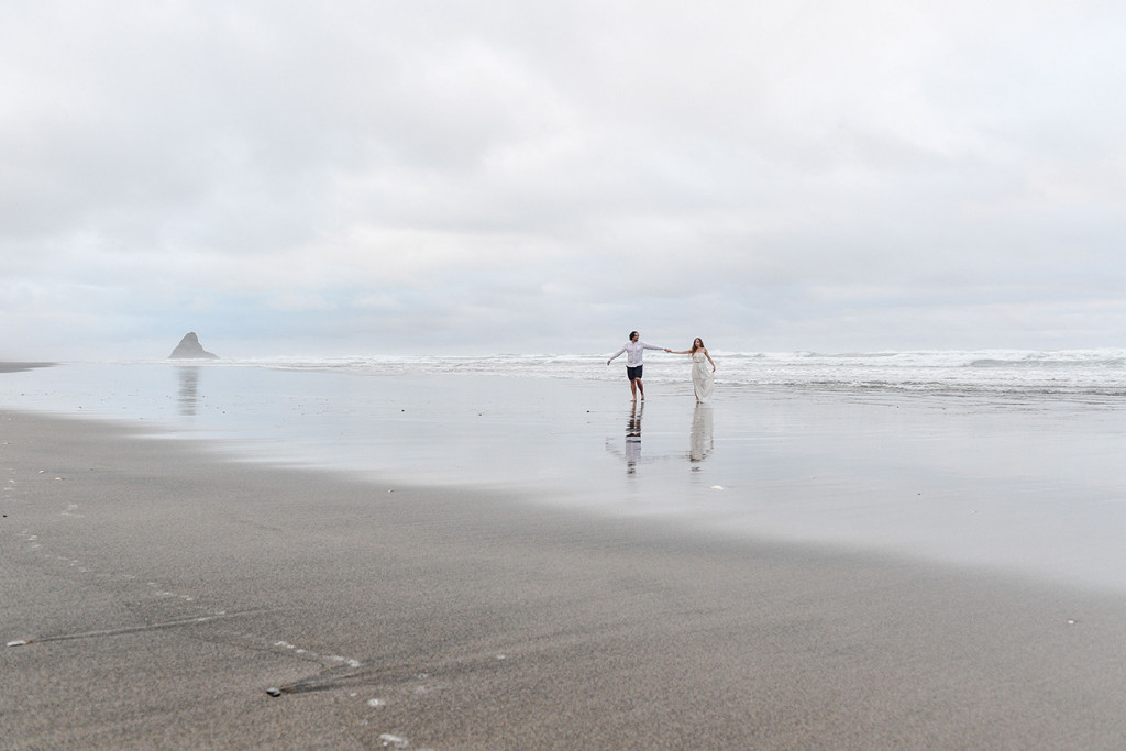 The newly married couple play in the sea at Karekare Beach NZ