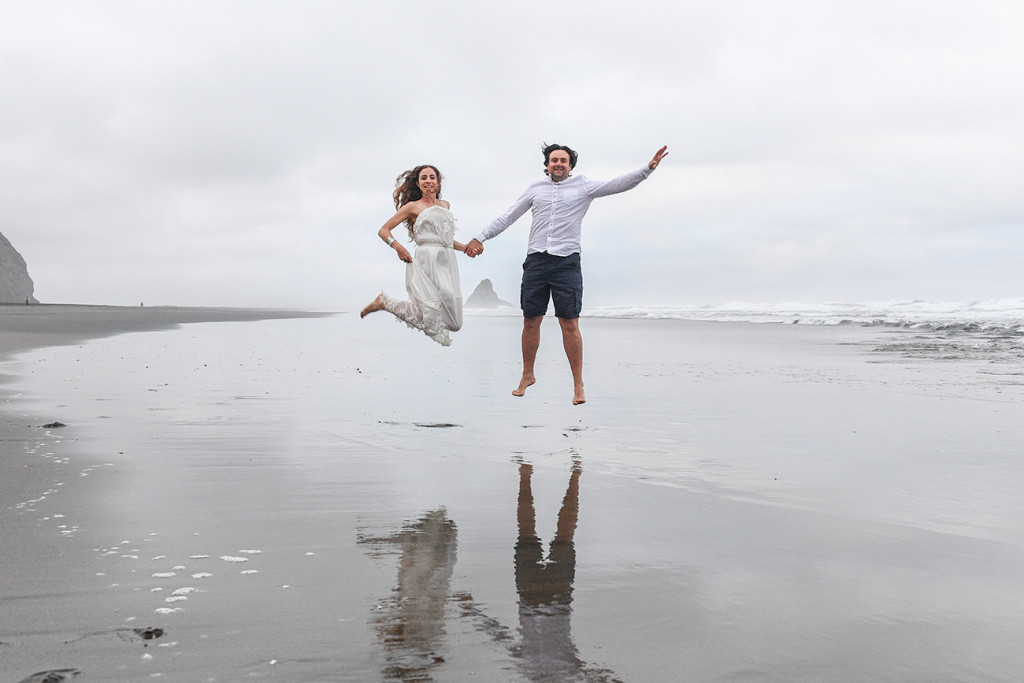 Newly eloped couple jump in black sand Karekare Beach Auckland NZ