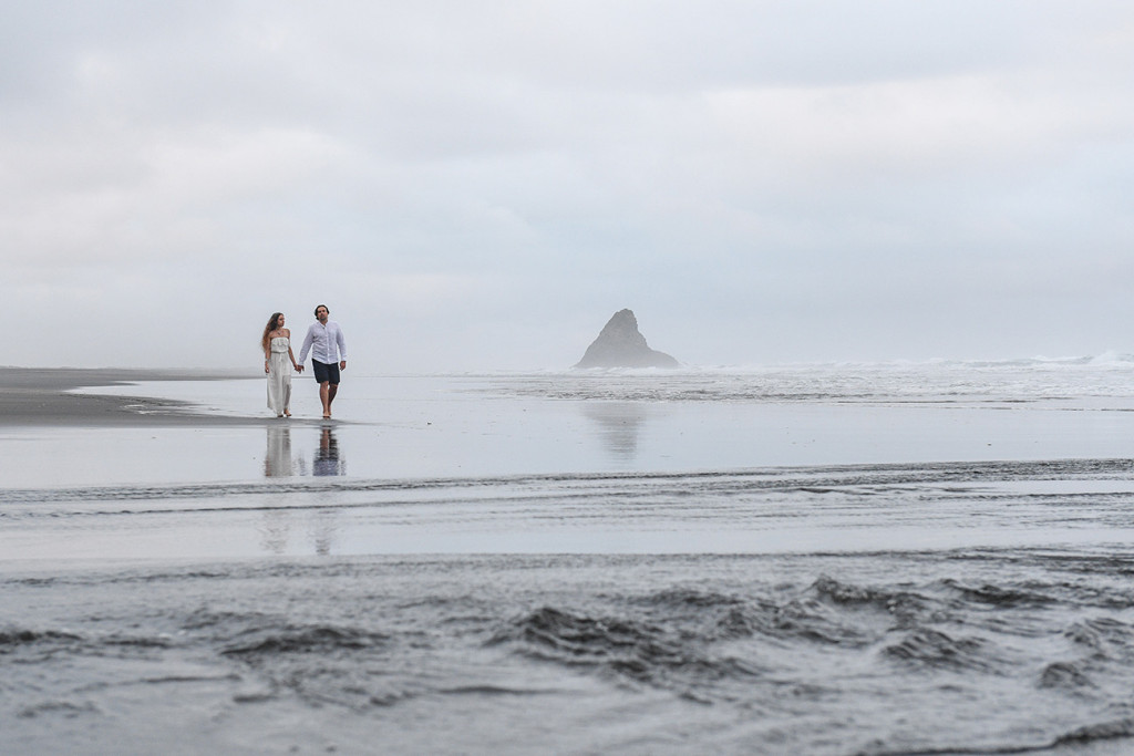 Newly eloped couple walk hand-in-hand in KArekare black sand Auckland