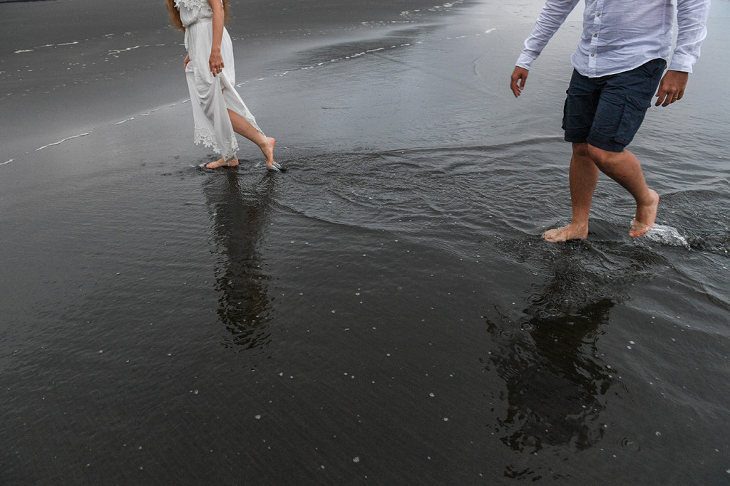 Married couple walk together in black sand beach Karekare NZ Auckland