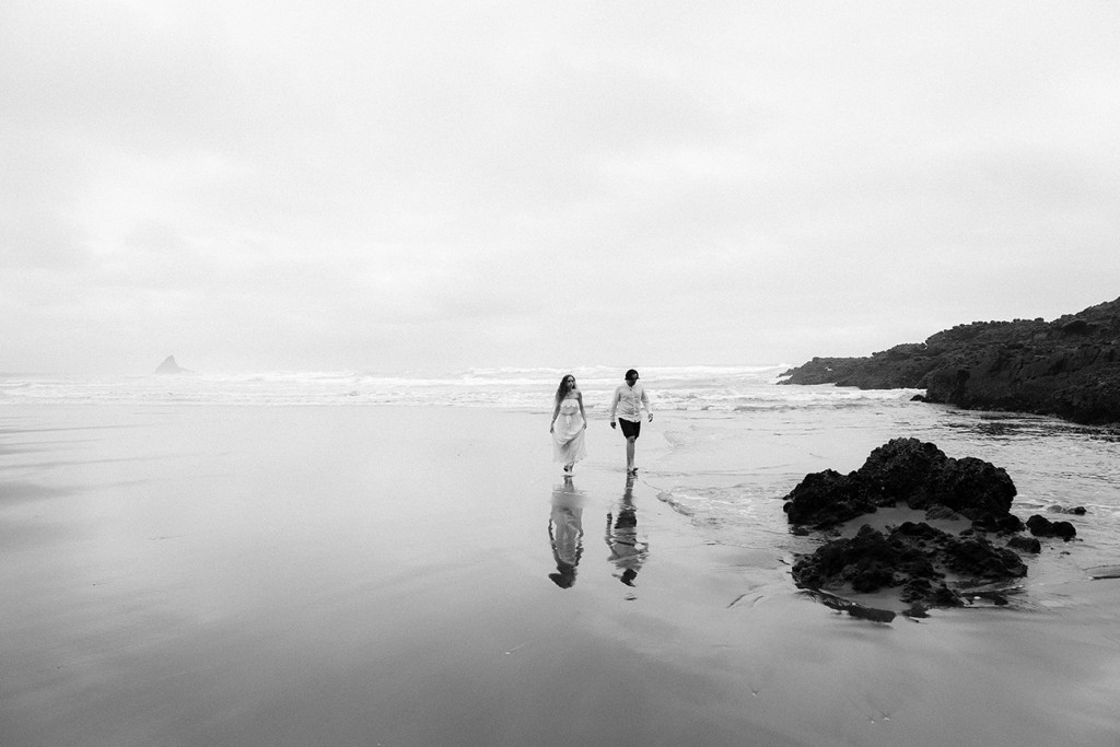 Black and white picture of newly eloped couple against stormy weather Karekare NZ