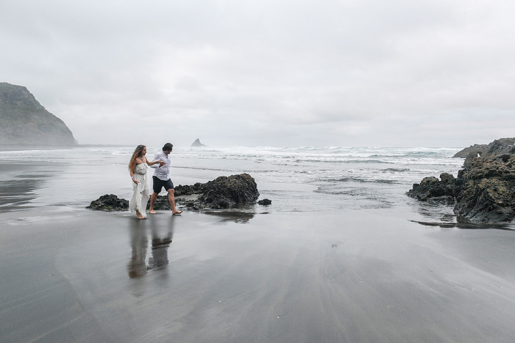 Eloped couple stroll against dull weather on black sand beach Karekare NZ Auckland