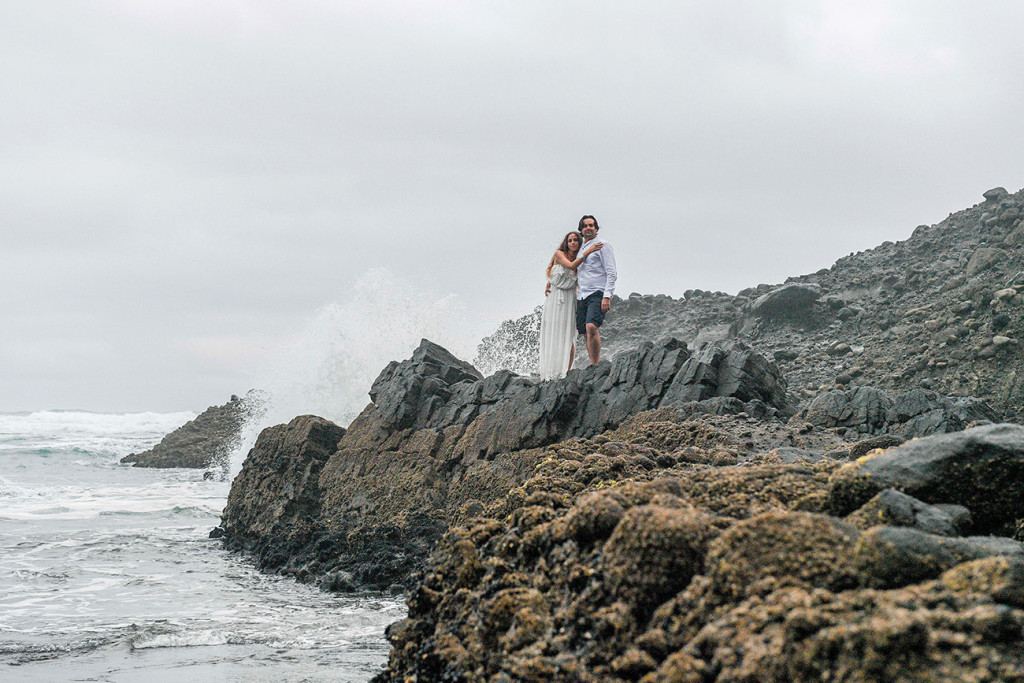 Newly married couple hug standing on rocks at Karekare NZ Auckland
