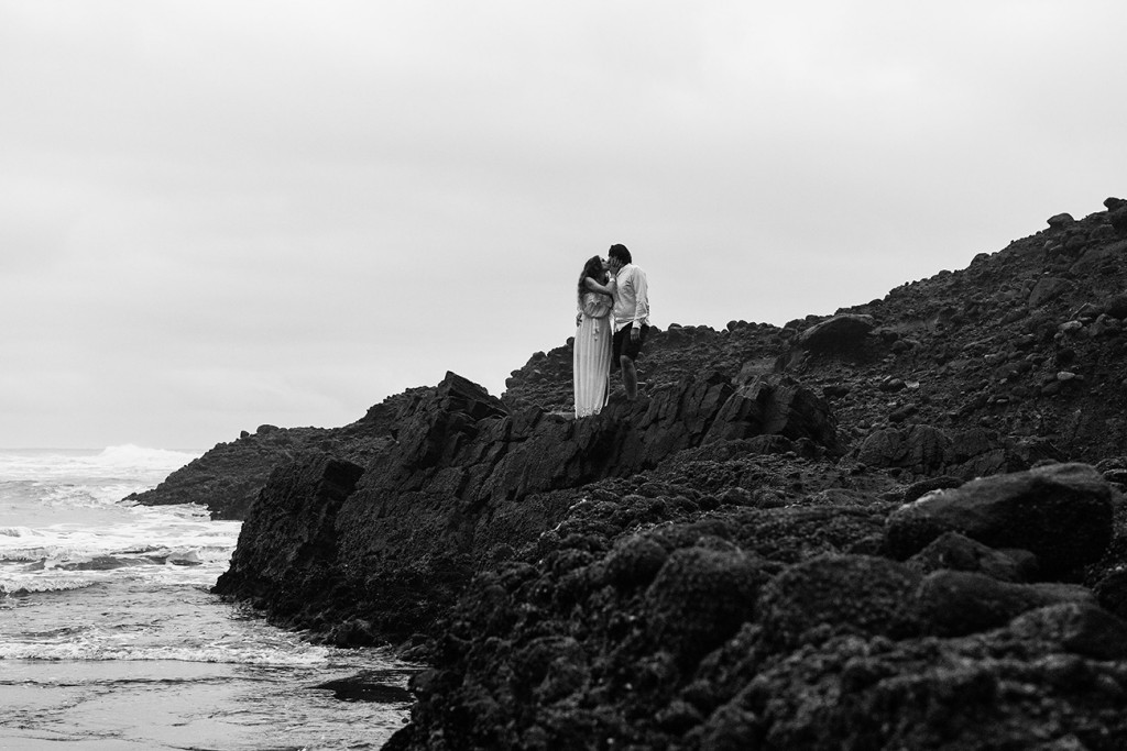 Black and white photo of newly eloped couple kissing on Karekare Beach NZ