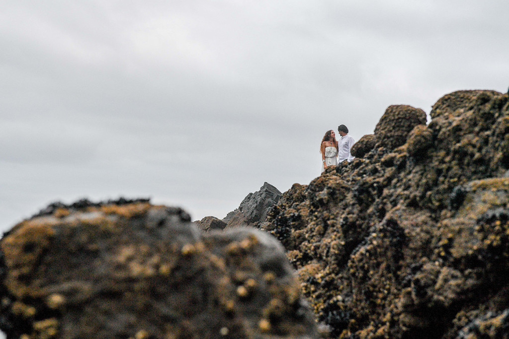 The couple seen in a distance at the black sand beaches of Karekare NZ