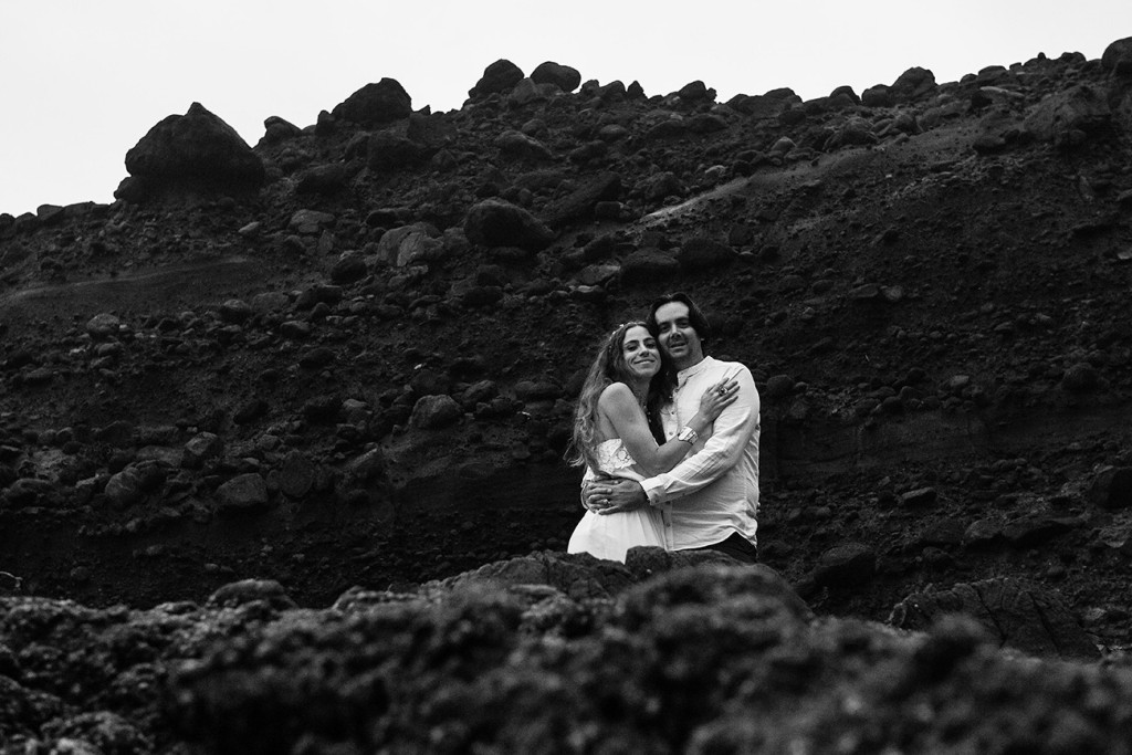Black and white photo of newly eloped couple cuddling in Karekare Auckland NZ
