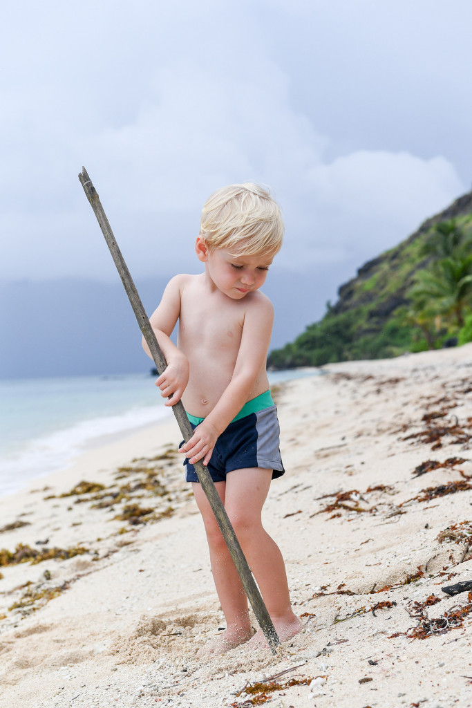 Young boy plays on Vomo Resort Beach at family Fiji wedding