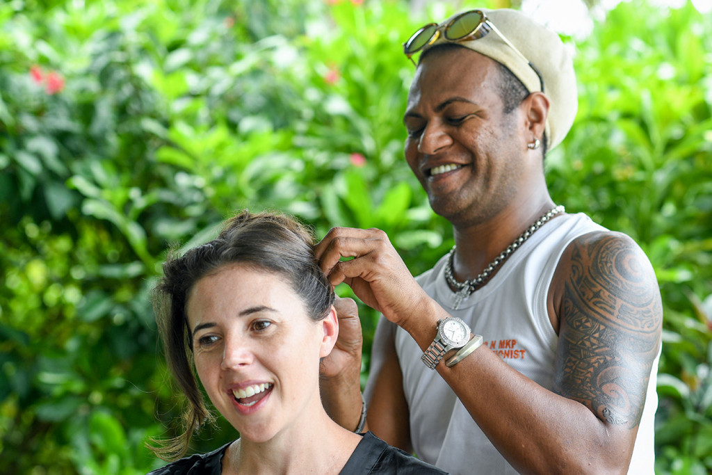 Hair artist and bride laugh during preparation for Vomo Island Resort