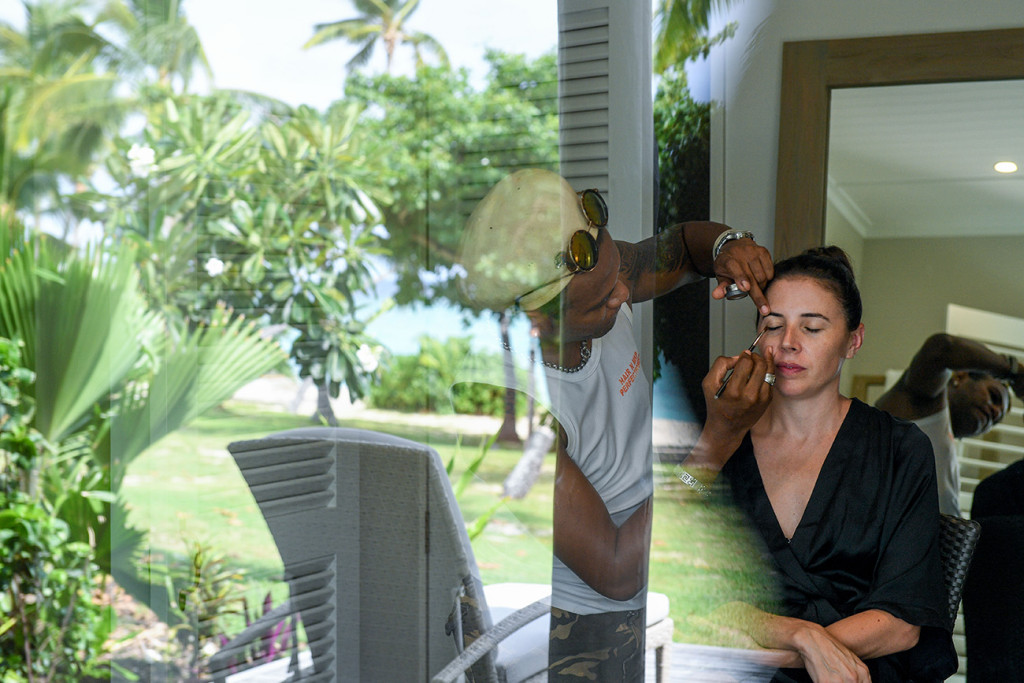 Reflection through window of bride's hair and makeup being touched up at Vomo Island Resort Fiji wedding