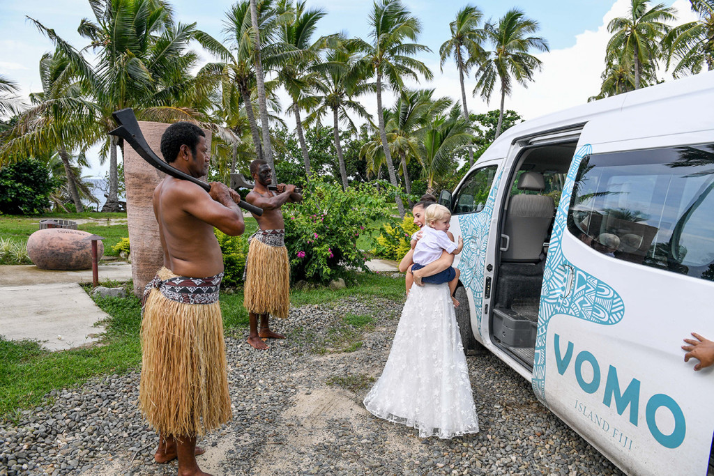 Traditional Fiji warrior look on as bride leaves Vomo Island Resort Fiji