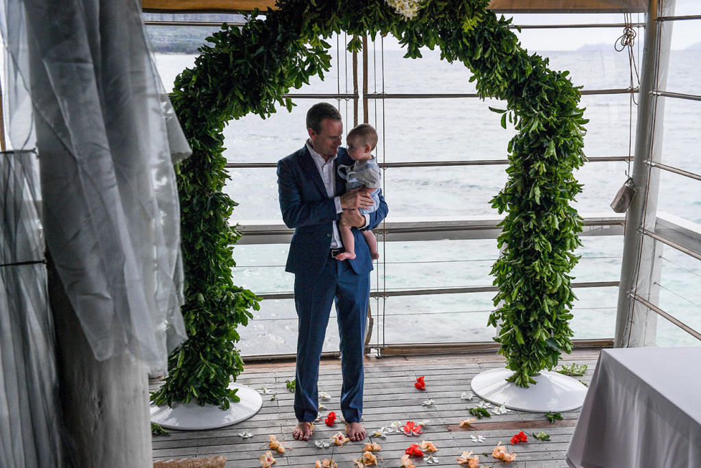 Groom holds son in his arms at the altar Vomo Island Resort