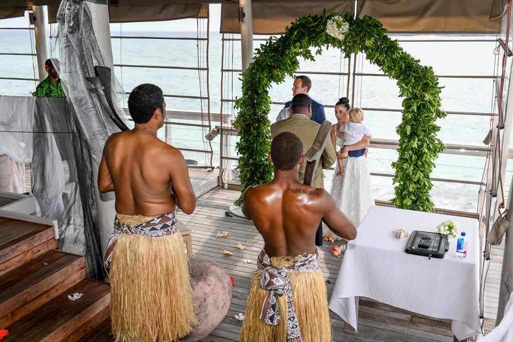 Fijian warriors watch on bride and groom at altar in family wedding Vomo Island Resort Fiji