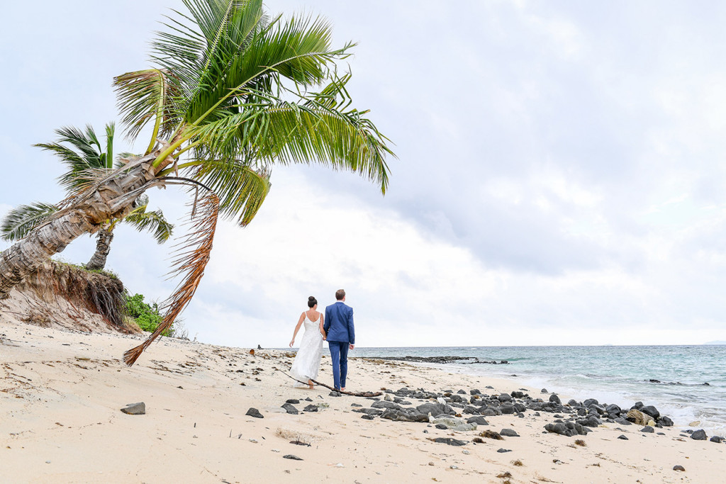 Couple walk by palm trees in Vomo Island Resort Fiji