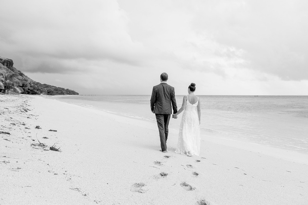 Black and white photo of couple walking down Vomo Island Resort Fiji beach