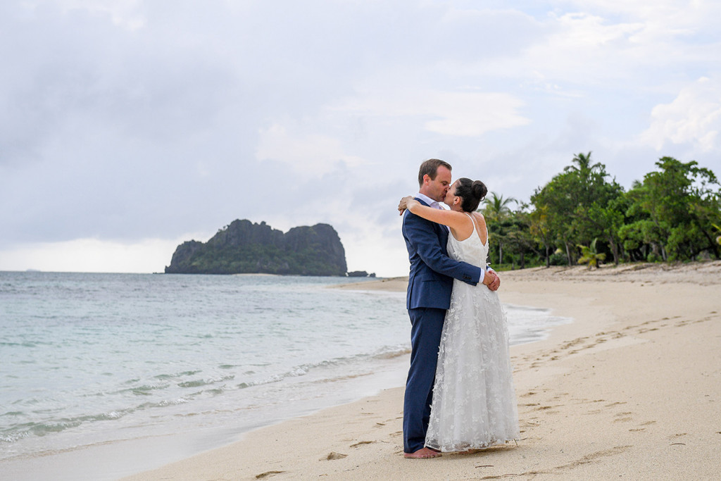 Married couple hug at beach in Vomo Island Resort Fiji wedding