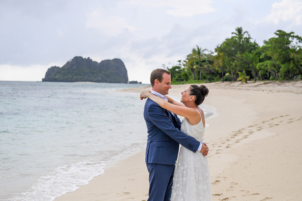 Couple hugs by the beach at the Vomo Island Resort Fiji wedding