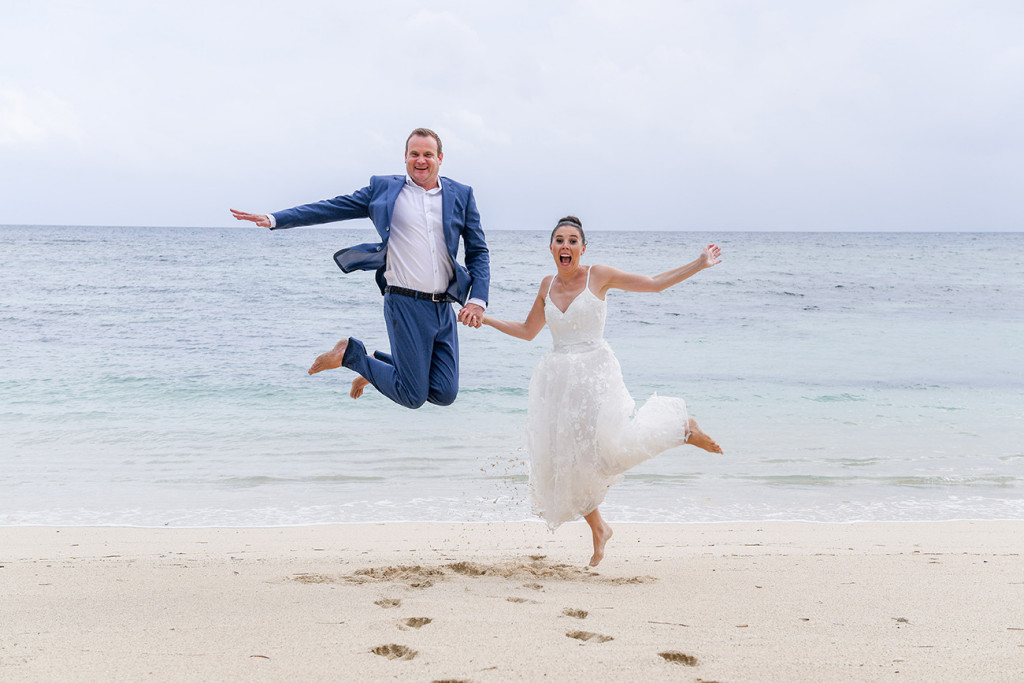 Couple happy jumps on the beach at Vomo Island Resort Fiji wedding