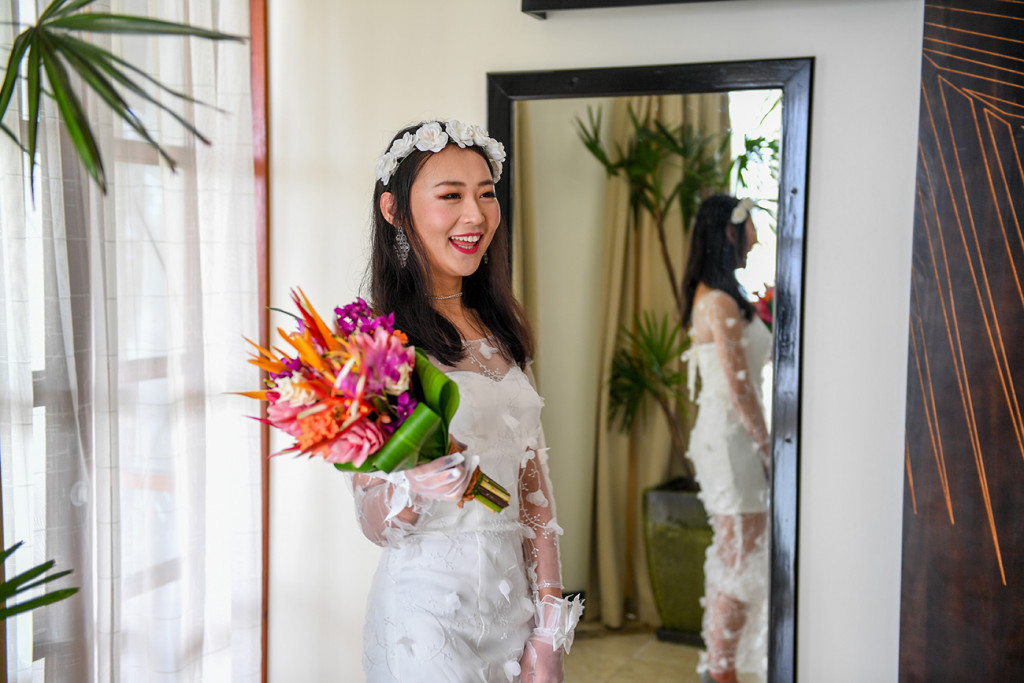 Stunning asian girl holds pink and orange bouqet in Warwick Fiji wedding